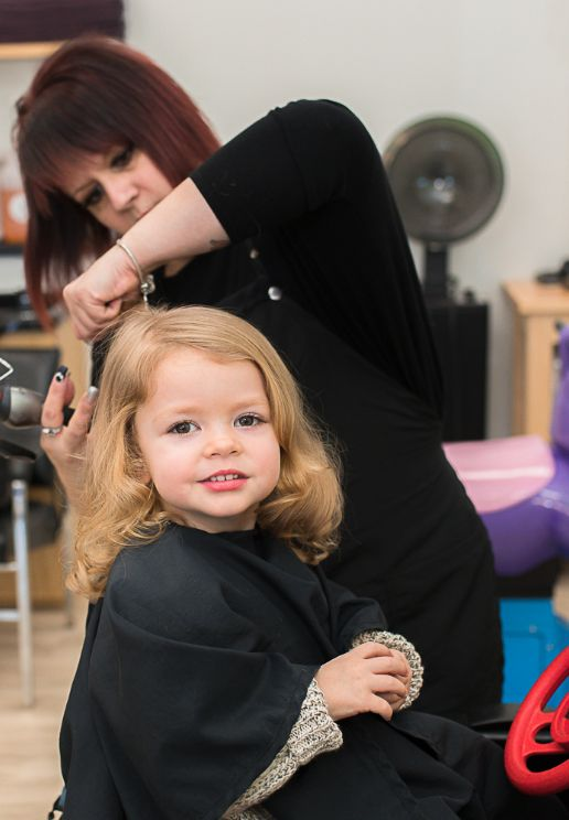 A Staff at Beaners fun cuts cutting a child's hair