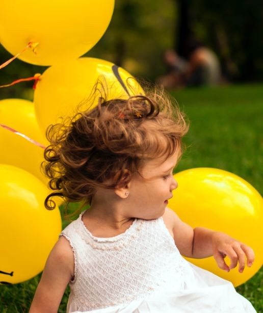 a happy kid with yellow balloons